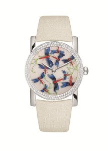 Brilliantly colored dragonflies scatter this pale cream watch.